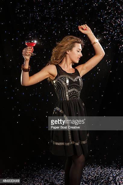Elegant lady in a black dress dancing in a club