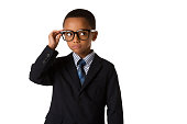 Elegant little man with glasses in business suit. Concept of leadership and success. Studio shot. Young boy posing.