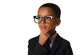Elegant little thoughtful african-american boy with glasses in business suit. Studio shot. Young boy posing. Copyspace