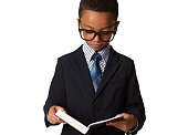Elegant little african-american boy with glasses in business suit hold the book. Studio shot. Young boy posing.