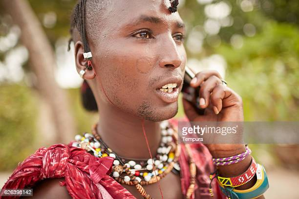 Elegant Maasai man using a smartphone.