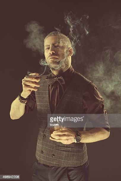 Elegant man drinking scotch whisky and smoking cigar