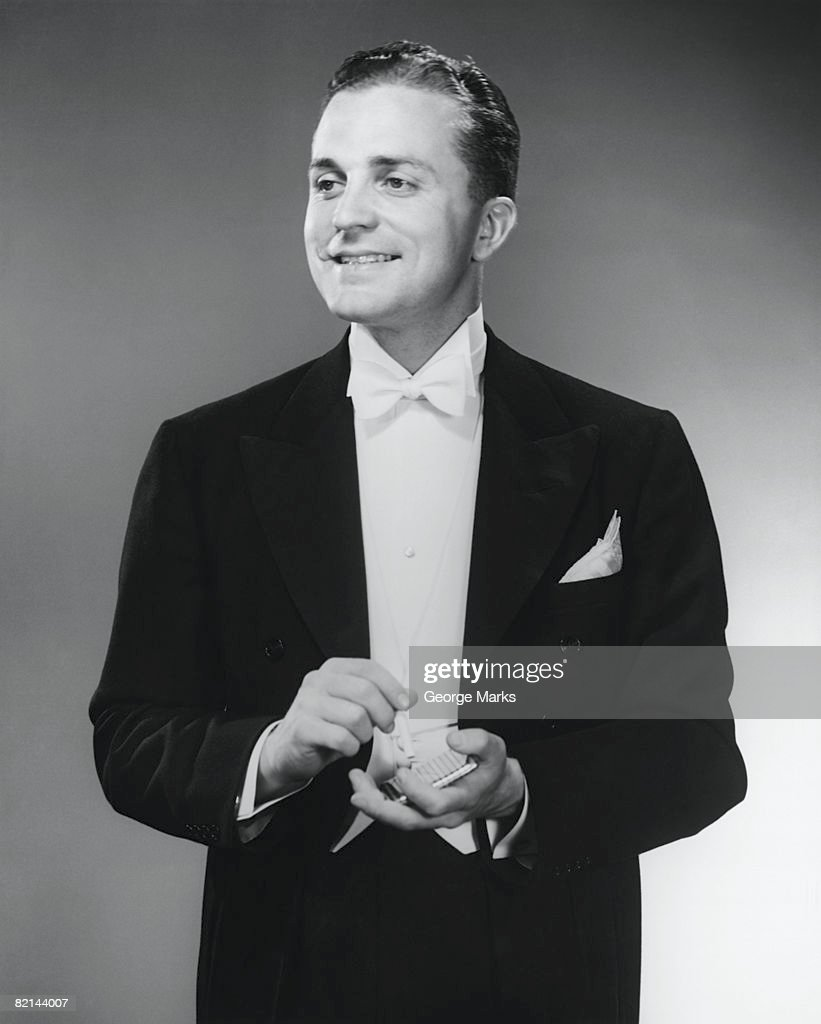Elegant man holding cigarette case, posing in studio, (B&W), portrait : Stock Photo