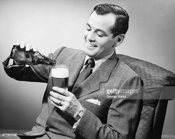 Elegant man pouring beer from bottle into glass, (B&W)