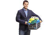 Elegant man with a laundry basket full of clothes isolated on white background