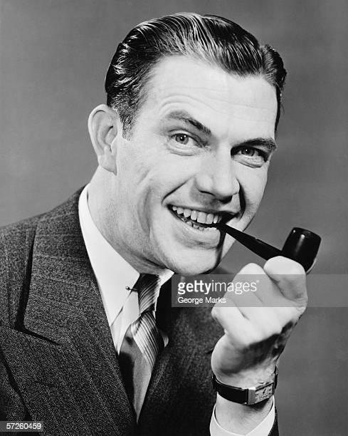 Elegant man with pipe posing in studio, (B&W), close-up, portrait