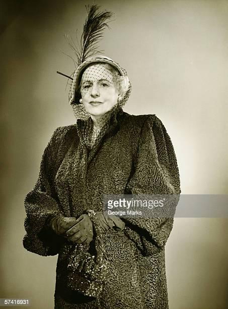 Elegante mujer madura en sombrero y posando en studio recubrimiento