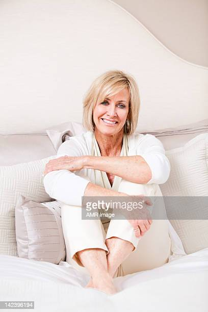 Elegant mature woman sitting with her arms and legs crossed