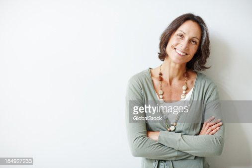 Elegant middle aged woman with her arms crossed against white