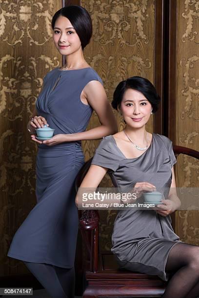 Elegant mother and daughter enjoying tea