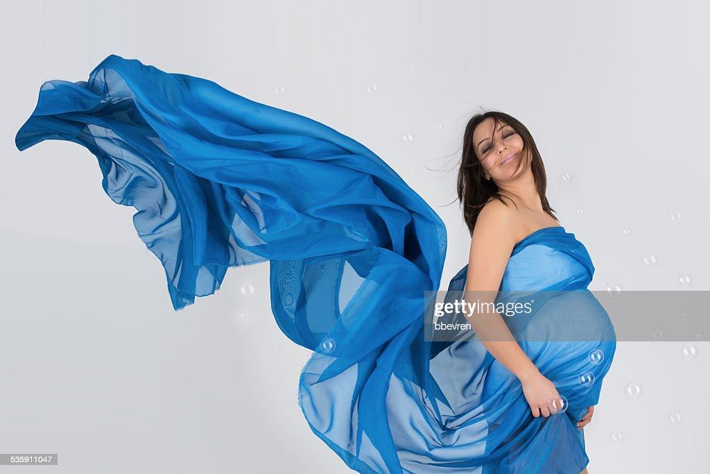 Elegante mãe grávida em Vestido azul Posando onduladas : Foto de stock