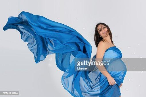 Mamá embarazada en elegante vestido azul posando ondulado : Foto de stock