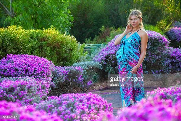 Élégante femme enceinte parmi les fleurs violet des parterres
