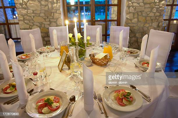 Elegant restaurant, table covered, evening mood, appetizers on white plates