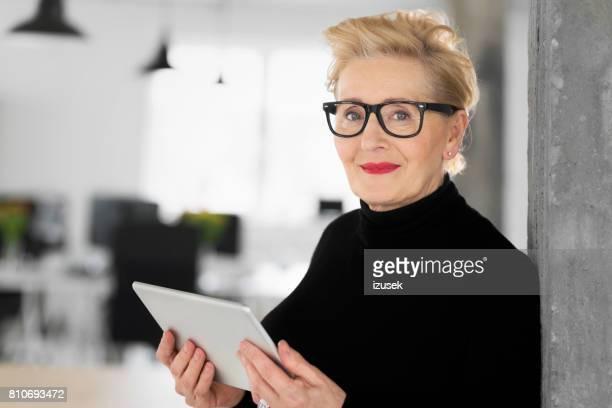 Elegant senior businesswoman using a digital tablet in the office