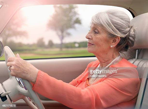 Elegant senior woman driving in car