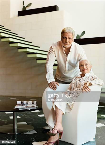 Elegant Senior Woman Sitting in an Armchair By a Coffee Table in a Modern Home, With Her Husband