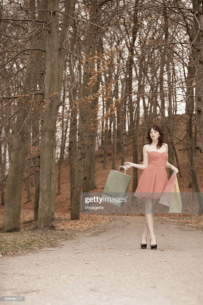 Elegant shopper woman walking in park after shopping : Stock Photo