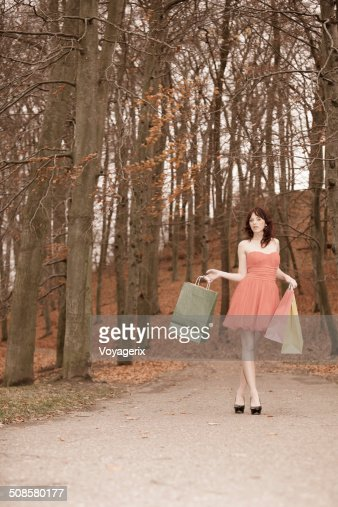 Elegant shopper woman walking in park after shopping : Stockfoto