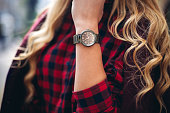 Elegant outfit. Closeup of wrist watch on the hand of stylish woman. Fashionable girl on the street. Female fashion.