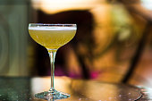 Whiskey Sour in an elegant martini glass against a colorful blurred background.