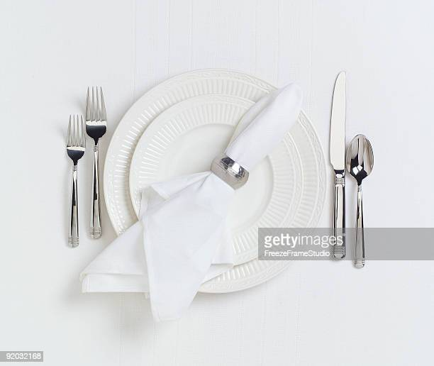 Elegant white dinner placesetting on white linen tablecloth
