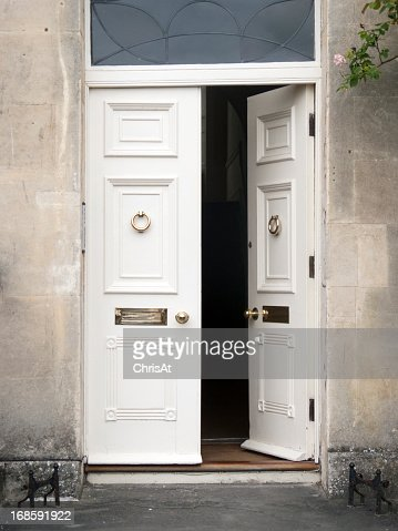 Elegant white doors with one open against a gray wall