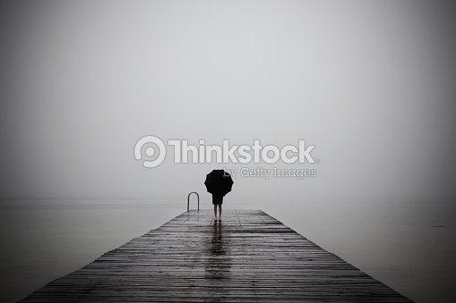 elegant woman dressed in black hiding with umbrella : Stock Photo