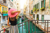 Elegant woman with red sunhat enjoys the view to a canal with passing by gondola in Venice, Italy