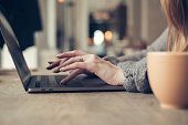 Elegant woman hands using laptop in the cafe