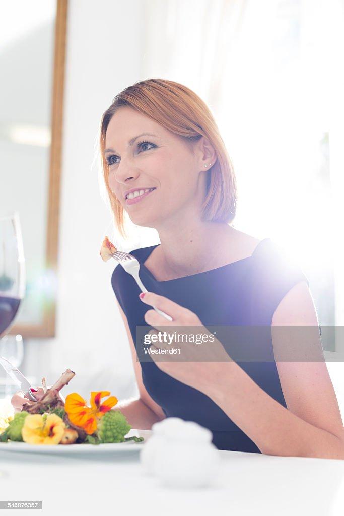 Elegant woman having dinner in restaurant : Photo