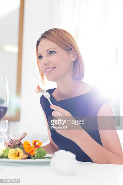 Elegant woman having dinner in restaurant