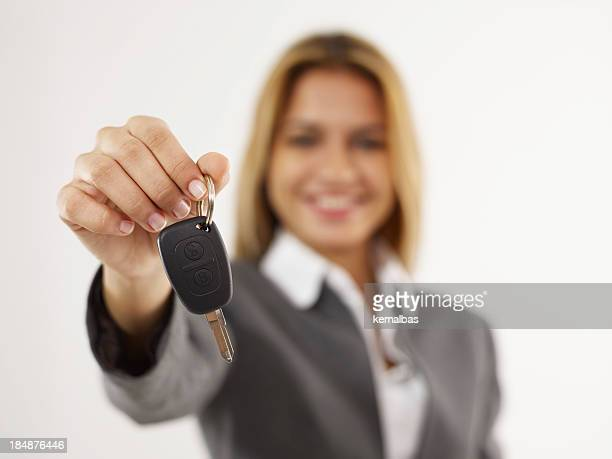 Elegant woman holding a car key with her right hand