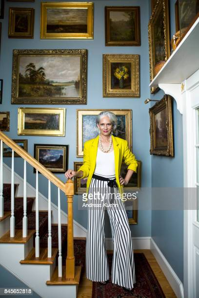 Elegant woman in a fashionable outfit with grey hair standing in a staircase with oil paintings on the wall.