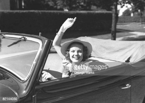 Elegant woman in convertible car, waving, (B&W), portrait : Stock Photo
