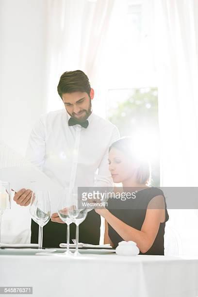 Elegant woman looking at menu in restaurant