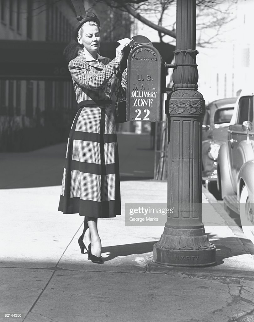 Elegant woman posting letter, (B&W) : Stock Photo