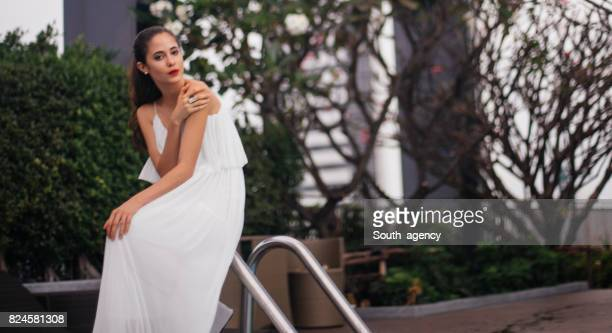 Elegant woman sitting by the pool