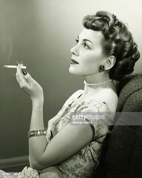 Elegante Frau Rauchen Zigarette, posieren in studio (B & W