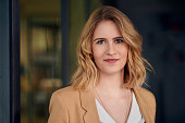 Portrait of smart elegant woman standing against dark background