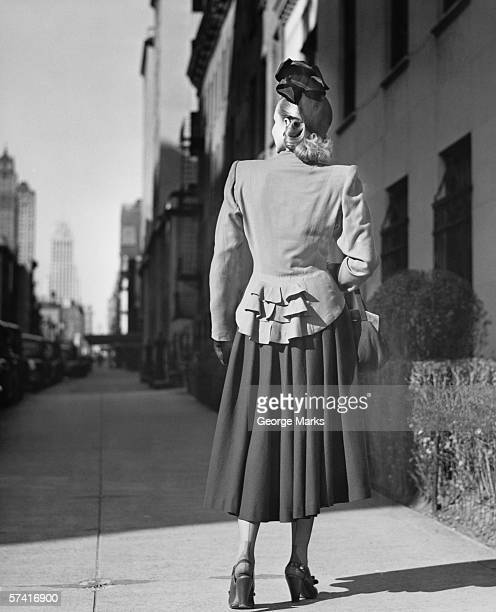 Elegant woman standing alone on sidewalk, Rear view, (B&W)