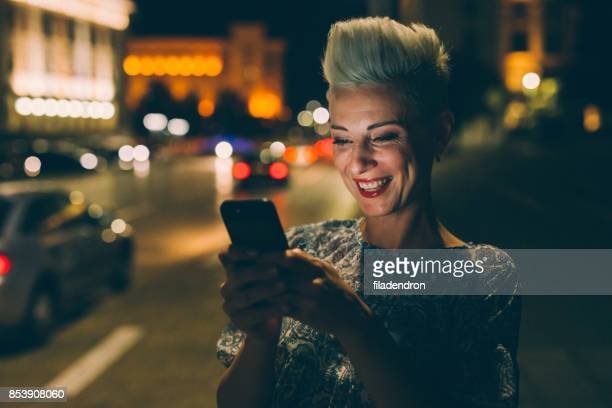 Elegant woman texting at night