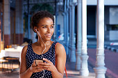 Portrait of elegant young black woman listening to music with smart phone and earphones