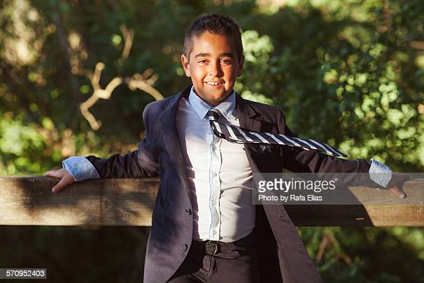 Elegant young boy leaning against fence outdoor