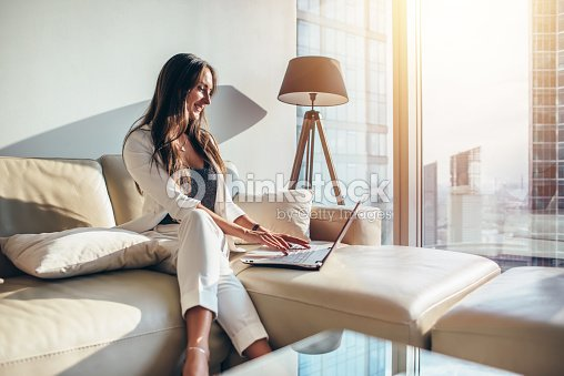 Elegant young female business woman using a laptop sitting on a sofa at home : Foto de stock