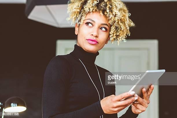 Elegant young woman holding digital tablet