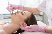Close up profile of pleasant girl is lying with closed eyes while beautician is doing microdermabrasion treatment at cosmetology cabinet. She is enjoying time in spa