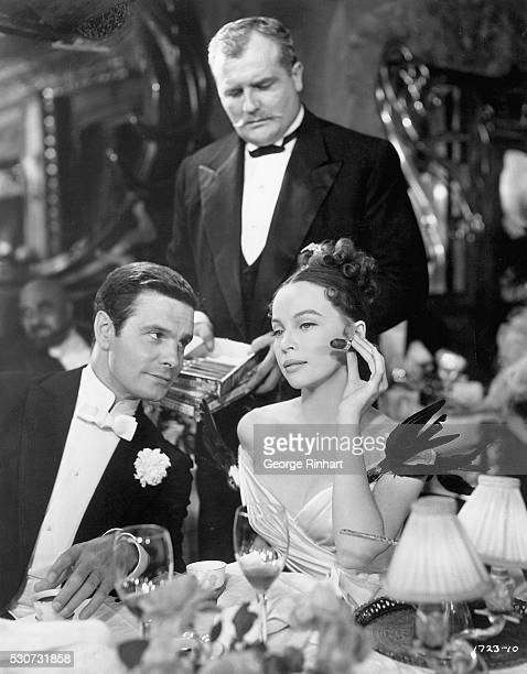 Elegantly dressed Leslie Caron chooses a cigar for Louis Jourdan in a scene from the 1958 MGM production of the film Gigi