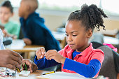 Elementary age African American girl building robot in science club