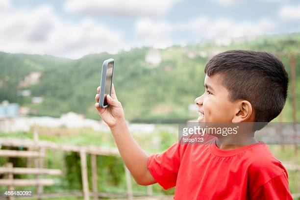 Elementary age, Asian boy using smart phone outdoors. Rural.
